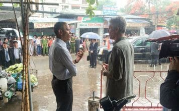 President Obama and Anothony Bourdain talking in the rain