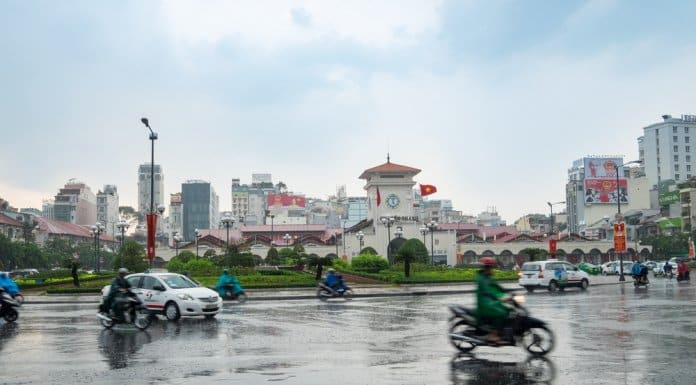Cars and motorcycles rush and running in the rain around Ben Thanh Market