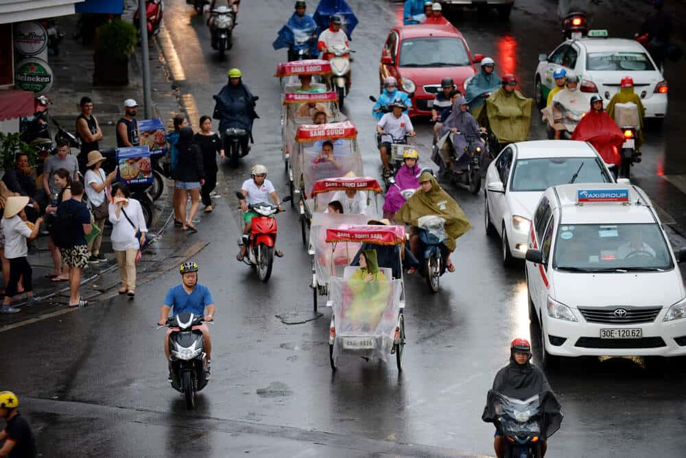 Cyclo carrying tourists to visit Hanoi old quarter as the summer afternoon rains. Vietnam rainy season