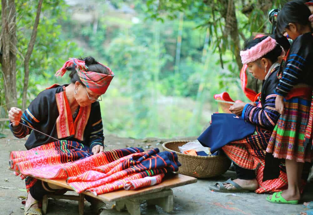 Hmong people are working with their traditional costumes