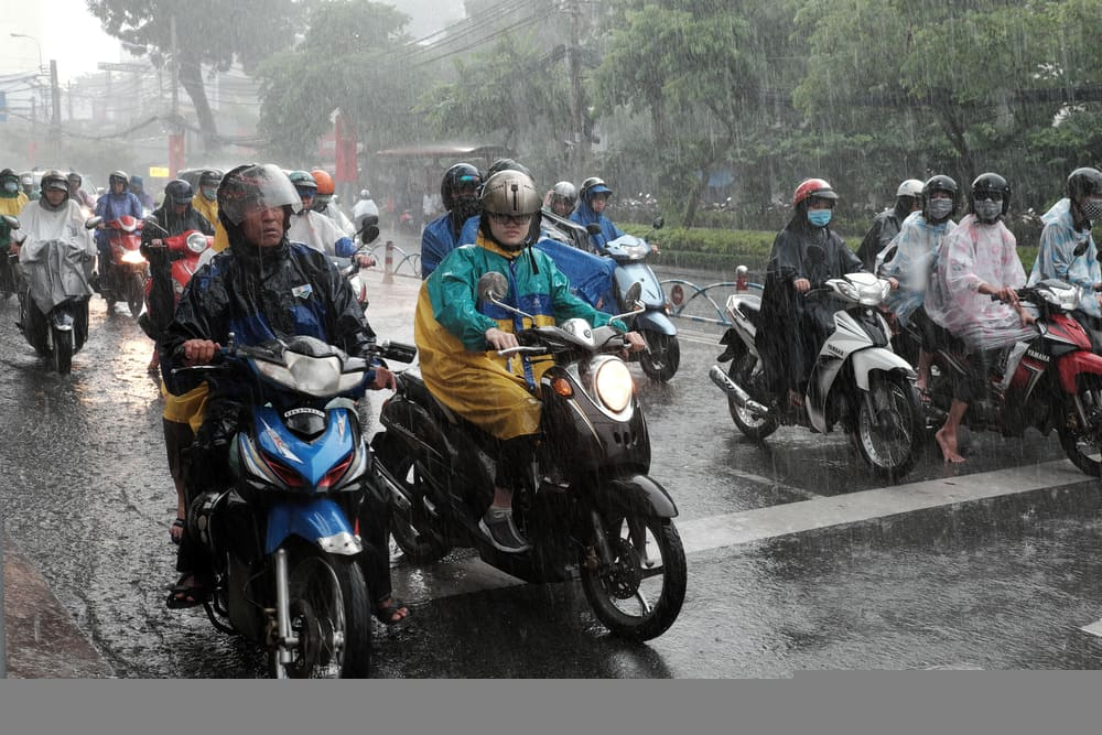 Vietnamese people wear helmet and raincoat ride motorbike in heavy rain, water on street, this time is Vietnam rainy season at Saigon